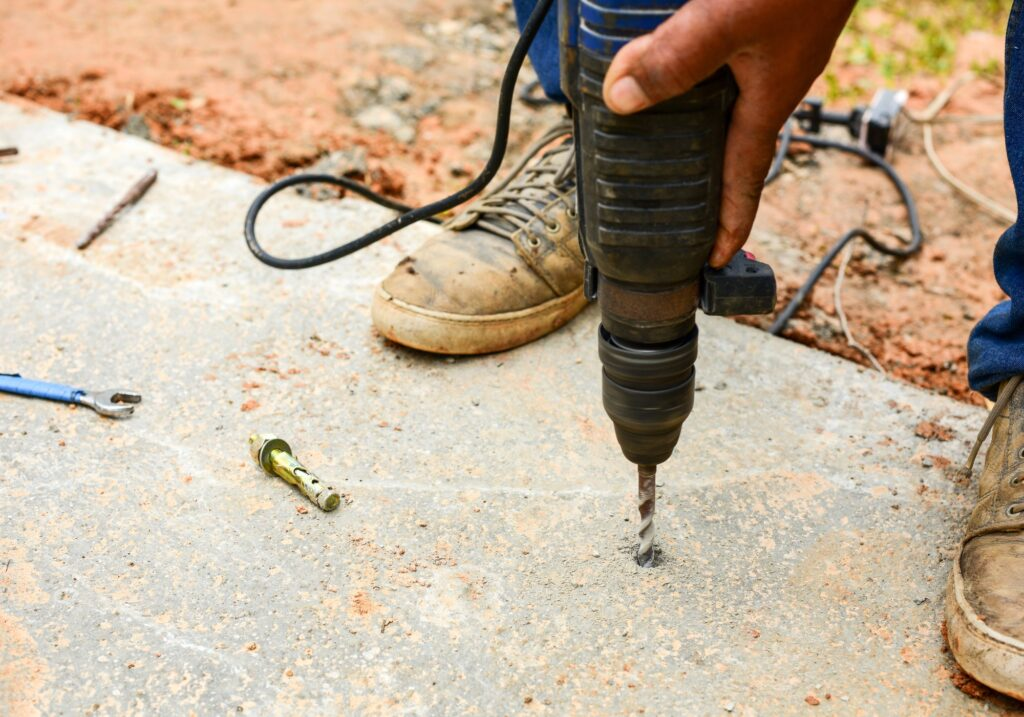 People using electric drill,He drilled concrete for steel anchor.